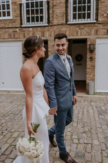 Bride in Roland Mouret wedding dress holding hands with her groom