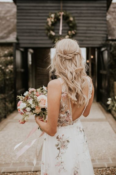 Bride in floral embroidered wedding dress with half up half down hairstyle