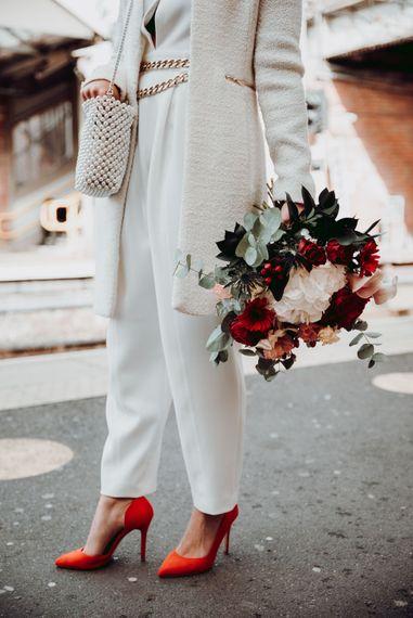 新娘穿着马西莫·杜蒂连衣裤,搭配红鞋和红白花束