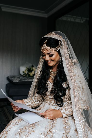 Bride on wedding morning reading a note from her groom in an Ivory gown and veil embellished with traditional Indian embroidery and gold work