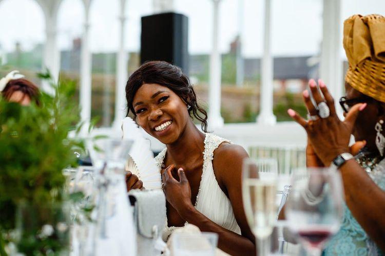 Bride in halter neck wedding dress smiling during the speeches