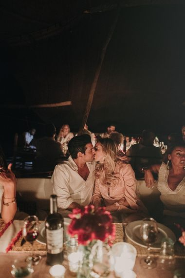 Bride and groom kissing at rehearsal dinner