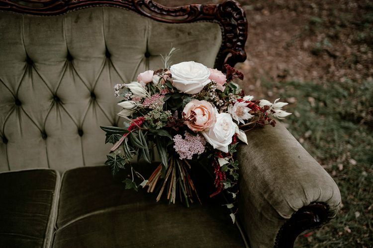 Blush pink and white wedding bouquet resting on a vintage couch
