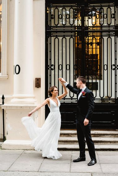 Bride and groom twirling in front of their wedding venue Carlton House Terrace