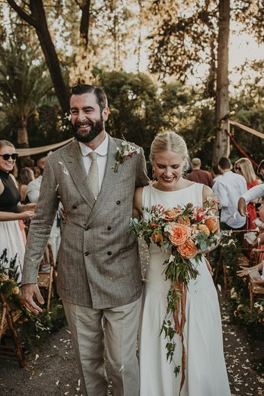 Bride holding a bouquet with coral flowers and groom wearing a double breasted jacket