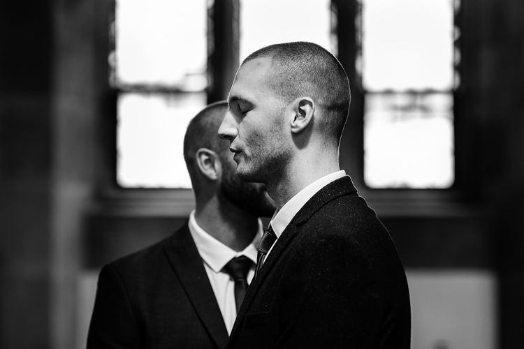 Black and white portrait of the groom at the altar