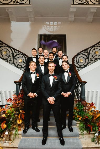 Groomsmen in black tuxedos gather on the stairs at Carlton House Terrace wedding