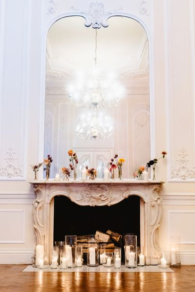 Flower stems in cases decorating the fireplace