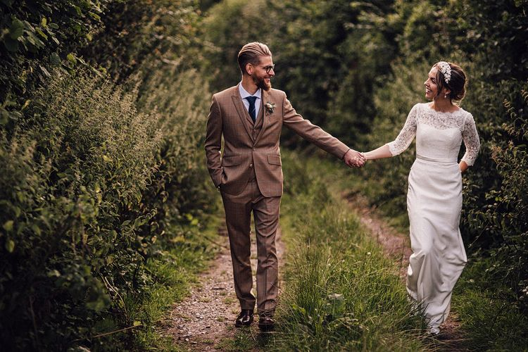 Bride and groom holding hands at The Long Barn, Hampshire wedding