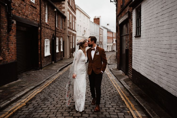 Bride and groom walking through Chester Town