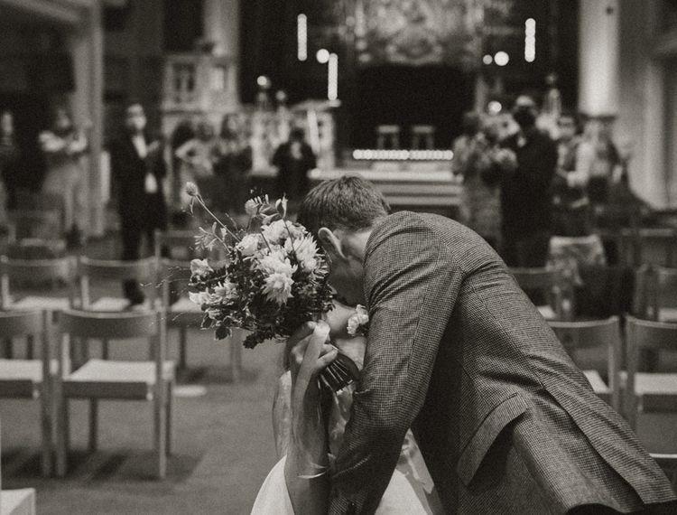 Groom in check blazer kissing his bride