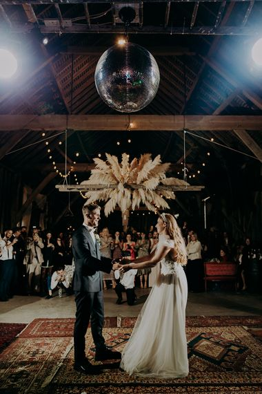 Bride and groom first dance under a disco ball