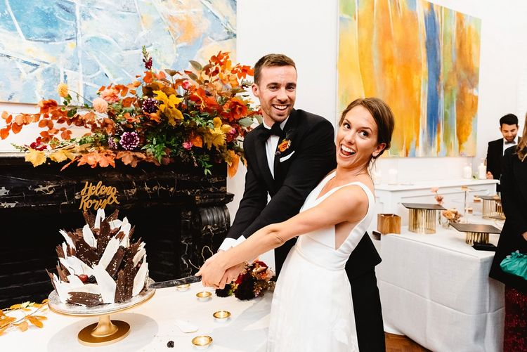 Bride and groom cutting the wedding cake at Autumn black tie wedding