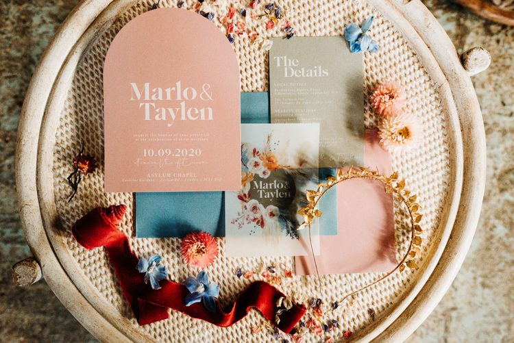Pink and blue wedding stationery resting on a wicker table