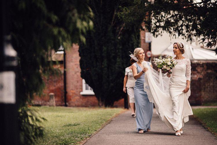 Bridesmaid holding the brides Sassi Holford wedding train