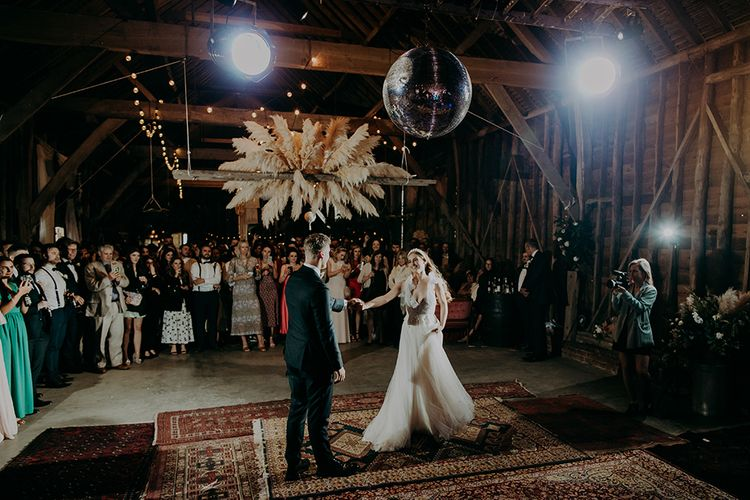 Bride and groom first dance in a barn with pampas grass floral installation
