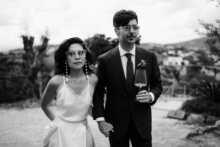 Black and white portrait of stylish bride and groom in shades holding hands