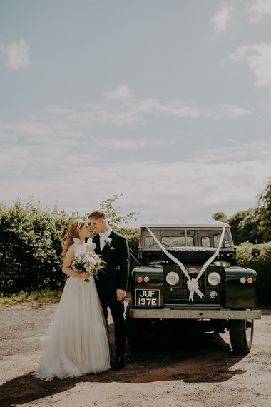 Bride and groom portrait by the wedding jeep