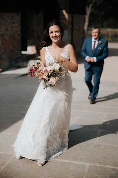 Beautiful bride in lace Madi Lane wedding dress holding her bouquet