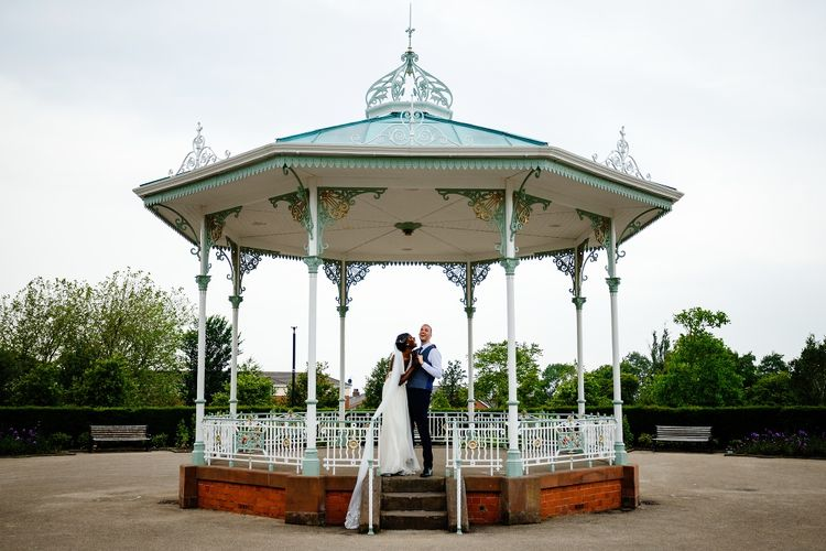Bride and groom portrait on the bandstand in Liverpool