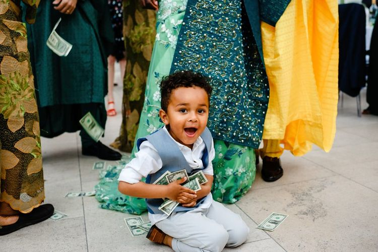 Little boy picking up the money at traditional Nigerian money dance