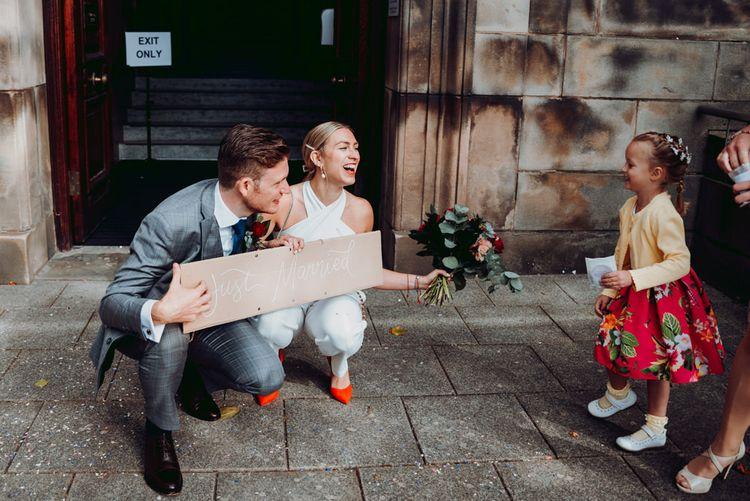 新婚新娘和新郎手捧一个DIY纸板箱标志