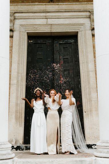 穿着休闲婚纱和两件碎布的新娘在避难所教堂外投掷五彩纸屑