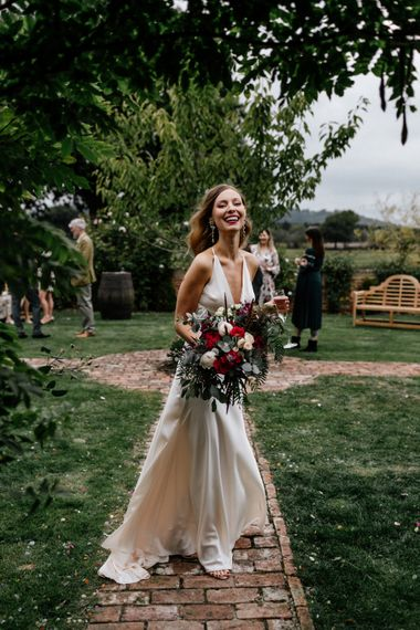Beautiful bride with read and white bouquet at Micro wedding