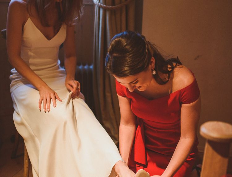Family member fitting bridal shoes for bride