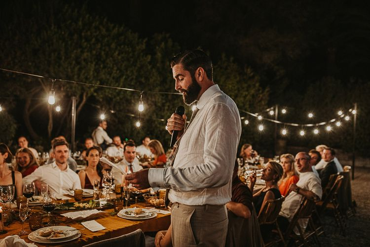 Groom delivering the speech at outdoor wedding