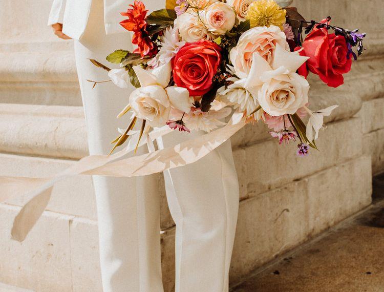 拿着一个明亮的色的婚礼花束的一件裤子衣服的新娘
