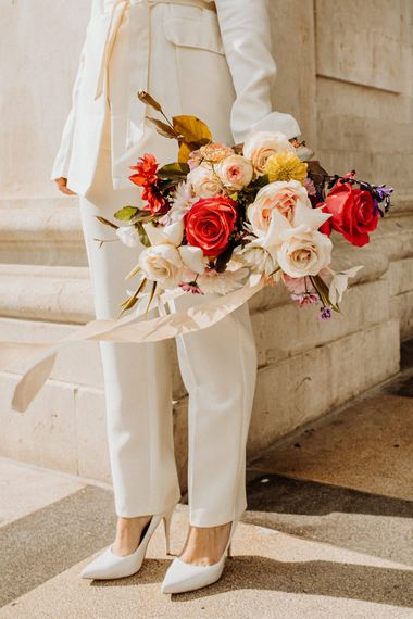 Bride in a trouser suit holding a brightly coloured wedding bouquet