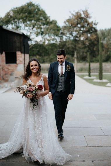 Bride in lace wedding dress and groom in navy suit