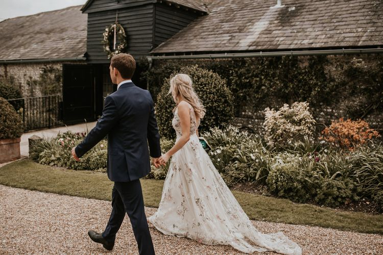 Bride and groom holding hands at their wedding venue Upwaltham Barns