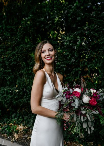 Stylish bride in ASOS wedding dress holding a red and white bouquet