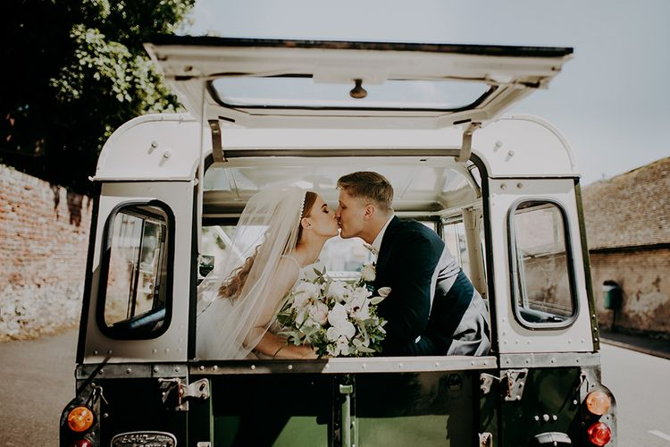 Bride and groom kissing in their jeep wedding car