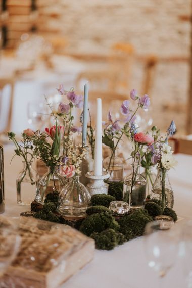 Botanical centrepiece with floral stems in jars and moss