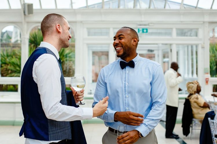 Groom and wedding guest laughing