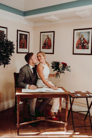 新娘穿着马西莫·杜蒂连衣裤,坐在新郎膝盖上签名登记