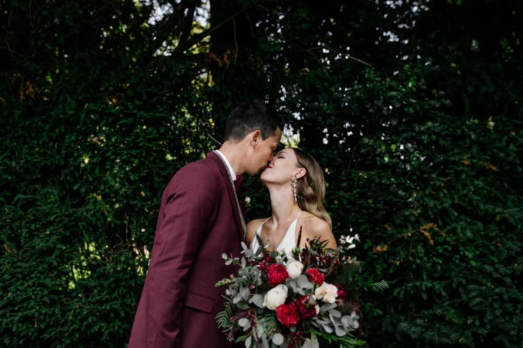 Groom in burgundy jacket kissing his bride