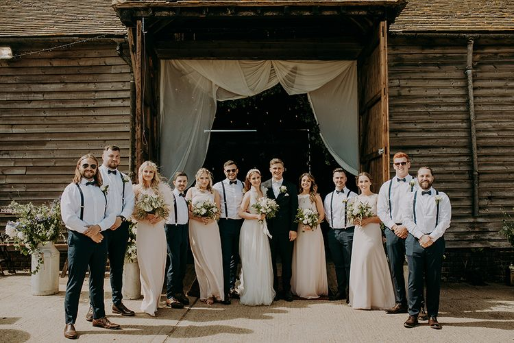 Wedding party portrait with bridesmaids in pink dresses and groomsmen in braces