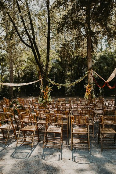 Outdoor forest wedding ceremony with wooden chairs and floral garland