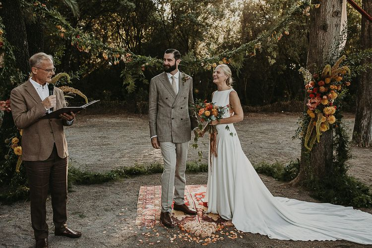 Bride and groom standing on a moroccan rug during woodland wedding ceremony