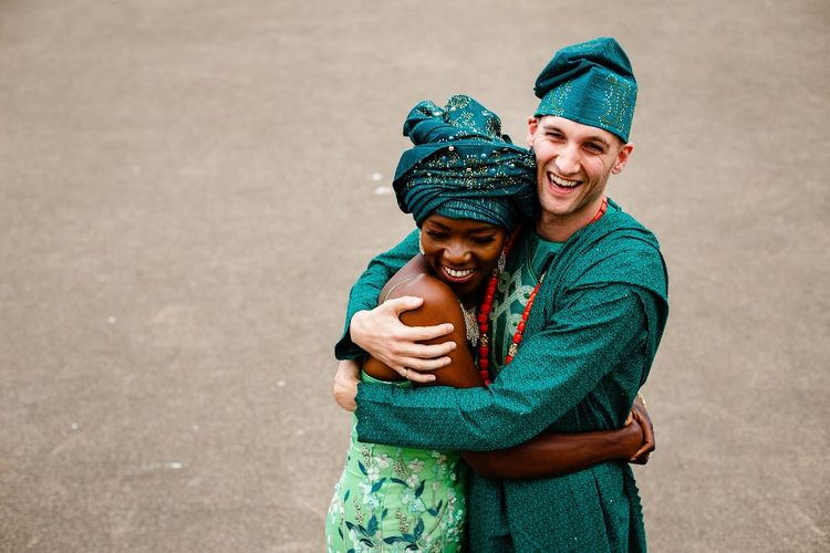 Bride and groom embracing in traditional Nigerian outfits
