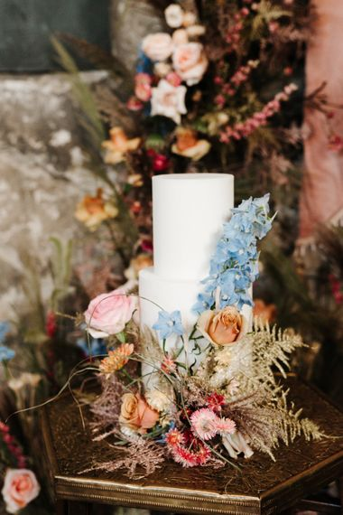 all white wedding cake decorated with colourful wedding flowers