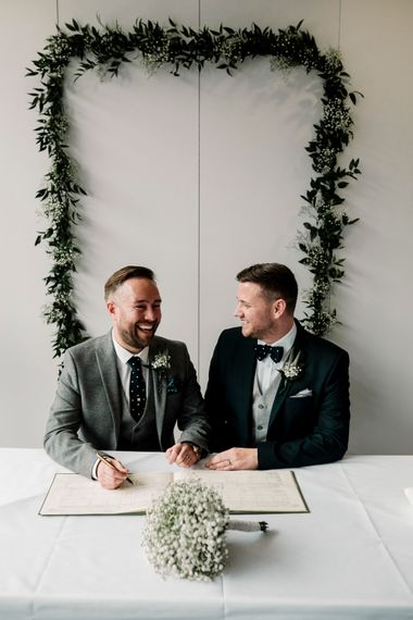 Groom and groom signing the register with greenery backdrop