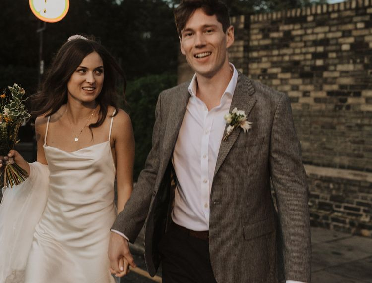 Groom in checked blazer and bride in slip wedding dress crossing the road at dusk
