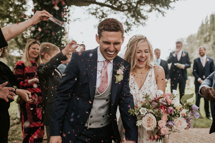 Bride and groom laughing during their confetti exit