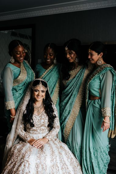 Bridal party on wedding morning in ivory and gold dress gown and green and gold sari's