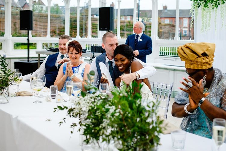 Groom kissing his bride at the top table